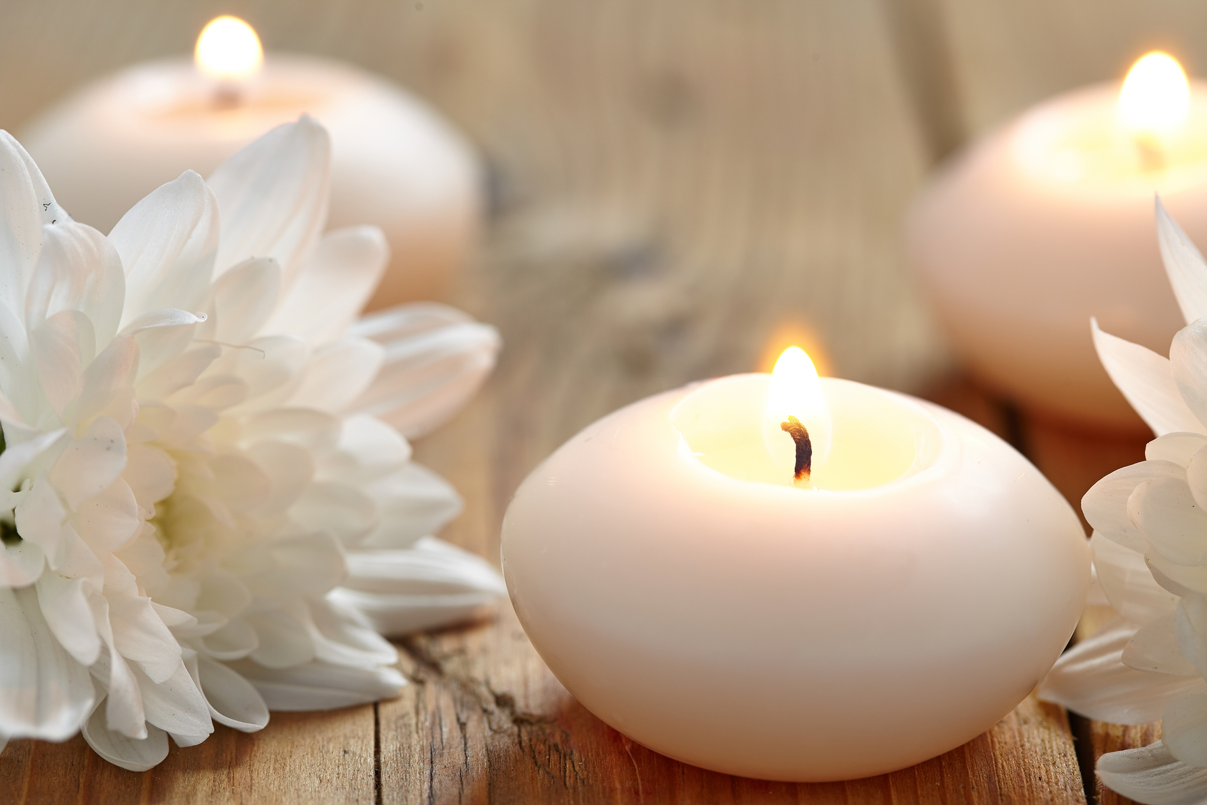 Candles and flowers on wooden table